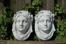 Two graceful female Caryatid wall ornaments of concrete
