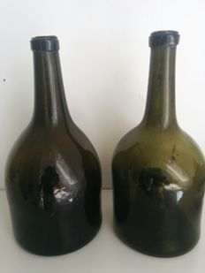Two hand-blown dark green glass wine bottles, with high pontil. Southern Netherlands, late 18th century