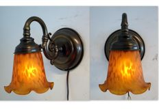 A pair of brass wall lamps with vintage glass lamp shades.