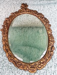 Antique facet-cut mirror in copper frame featuring Cupid