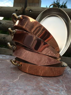 Five red copper pans with two brass ears.