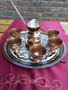 An engraved red copper tea service