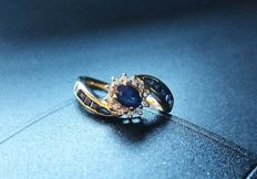 Ring in 18 kt gold of nice thickness, weighing 4.20 g, with 12 diamonds, a central sapphire and 10 other sapphires – 17 mm in diameter