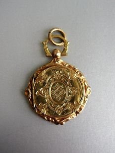 Round, gold medallion with scalloped edge and engraved  decoration