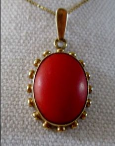 Pendant in 14 kt gold with a large red coral.