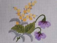 Hand embroidered tea tablecloth with mimosas and violets.