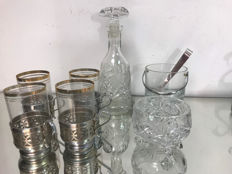 A set of four glasses in silver plated baskets, glass for ice with tongs, sugar bowl and crystal decanter.