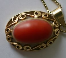 Gold necklace with pendant set with red coral