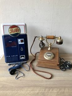 Two old telephones, one wooden PTT telephone and a Pepsi Cola telephone from the 1990's