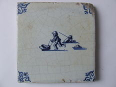 Antique tile with a winter scene on the ice.