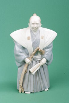 Porcelain sculpture in kimono with Japanese Samurai swords and a fan