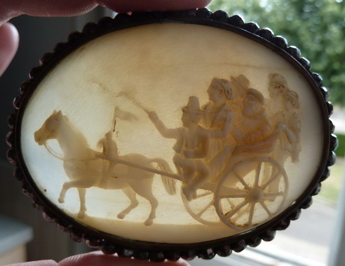 Shell cameo brooch depicting a scene of villagers going to a party