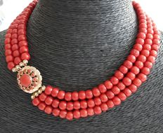 Necklace with three rows of coral and a large gold clasp