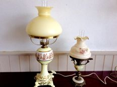 Two elegantly decorated oil lamps.