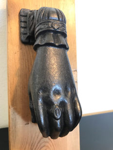 Robust cast iron door knocker in the shape of a hand with sphere, circa 1930