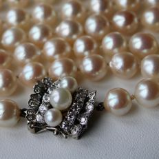High-grade 2-row pearl necklace of approx. 93 cm with 103 natural sea/salty pearls of approx. 7.4–7.7 mm, clasp with 10 large brilliant cut diamonds, approx. 0.46 ct and 12 smaller ones, approx. 0.08 ct, G/VVS1