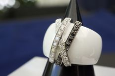 Gorgeous and deluxe contemporary ring made up of shiny white ceramic and 3 criss-crossed shanks in 18 kt white gold set with brilliant-cut diamonds (approx. 0.15 ct) including one row of black diamonds