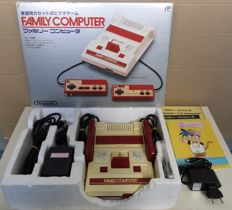 Boxed Nintendo Famicom console (Japanese import) with universal power supply and 3 Japan-exclusive games