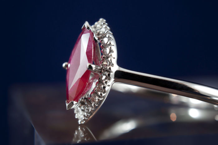 Superb rhodium-plated 18 kt white gold ring set with a certified Marquise-cut Ruby of 0.67 ct and its entourage of diamonds set in micro-prongs for a total of 0.15 ct.