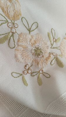 Square tablecloth with handmade embroidery, stranded lamé wires and details in yarn.