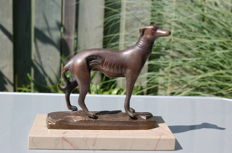 A bronze hunting dog on a marble base.
