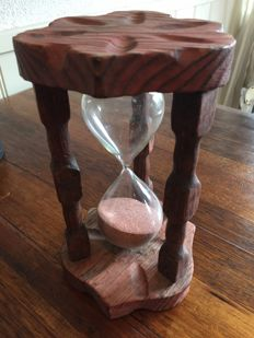 Wooden hourglass with carved columns and leafs and red and sand.