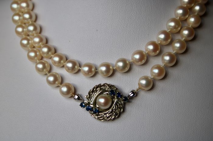Pearl necklace with sealt/salty ivorywhite-rosé of a very good quality Japanese Akoya round pearls (AA) ca. 7 mm. White gold lock with blue Sapphires.