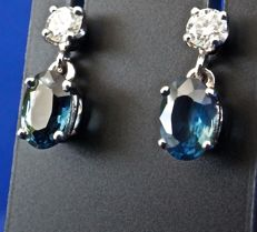 Natural oval transparent sapphires of 0.60 ct each, mounted in 18 kt white gold articulated earrings and topped with brilliant-cut diamonds of 0.10 ct each.