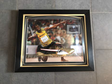 Usain Bolt, framed golden Puma spike shoe + photo of the moment of signing and with a certificate of authenticity