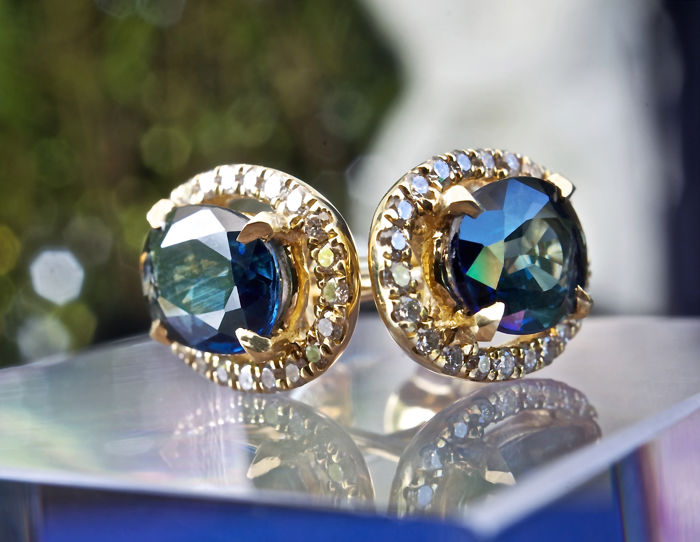 2 magnificent natural oval and transparent sapphires of 0.80 ct each, mounted in 18 kt yellow gold earrings and with entourage of brilliant-cut diamonds for a total of 0.24 ct.