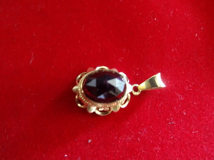 14 karat gold pendant with diamond cut garnet.