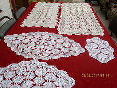 Lot of five white crocheted tablecloths made with fine yarn.