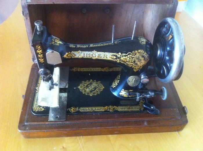 Singer sewing machine with a wooden cover, 1874