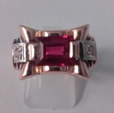 Gold women's ring set with ruby-red stone and two diamonds.