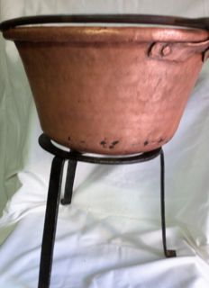 Antique copper cauldron with iron support