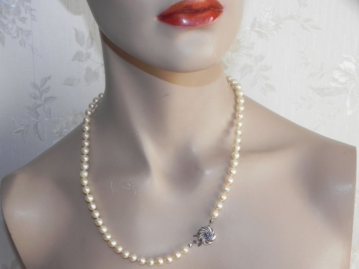 A pearl necklace made of Japanese Akoya salt water pearls 7.3 mm in diameter with a 585 / 14 kt white gold clasp with genuine sapphires