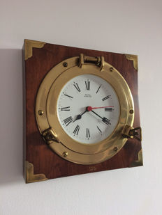 A Royal Marine ship's clock encased in a brass porthole on heavy wooden frame.