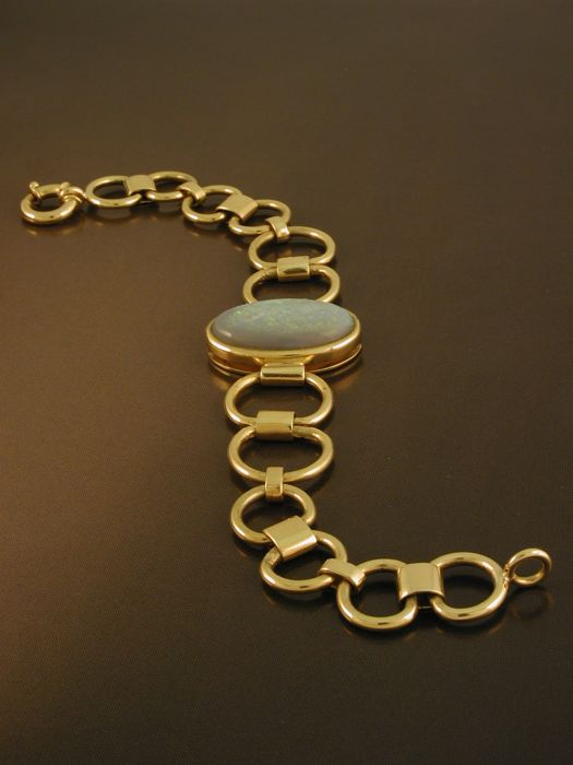 Bracelet in 18 kt/750 yellow gold, 18 kt, 750/1000, hallmarked, total weight:  34.20 g, central setting with oval cut opal 2.5 cm x 1.5 cm