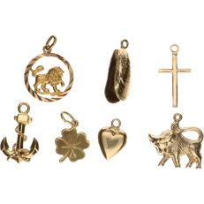 14 kt yellow gold pendants in a lot of 7. In the shape of a cross, heart, four-leaf clover, lion, buffalo, anchor, mussel - average length: 2.5 cm