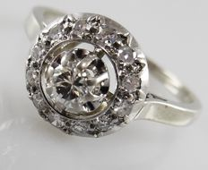 Platinum and 18 kt Art Deco entourage ring with diamonds, central diamond 0.16 ct, 0.40 ct in total.