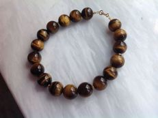 Bracelet made of tiger's eye, 27 grams, length 20.5 cm, 18 kt / 750 yellow gold clasp.