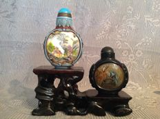 Two hand-painted Peking glass snuff bottles on wooden base - China - late-twentieth/early-twenty-first century