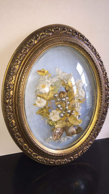 A richly decorated gold-coloured frame with convex glass, inside a bridal bouquet, France, first half 20th century