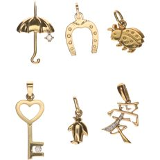 14 kt lot of 6 yellow gold pendants: a ladybug, horseshoe, penguin, umbrella with zirconia, key with brilliant cut diamond, Chinese character with brilliant cut diamond