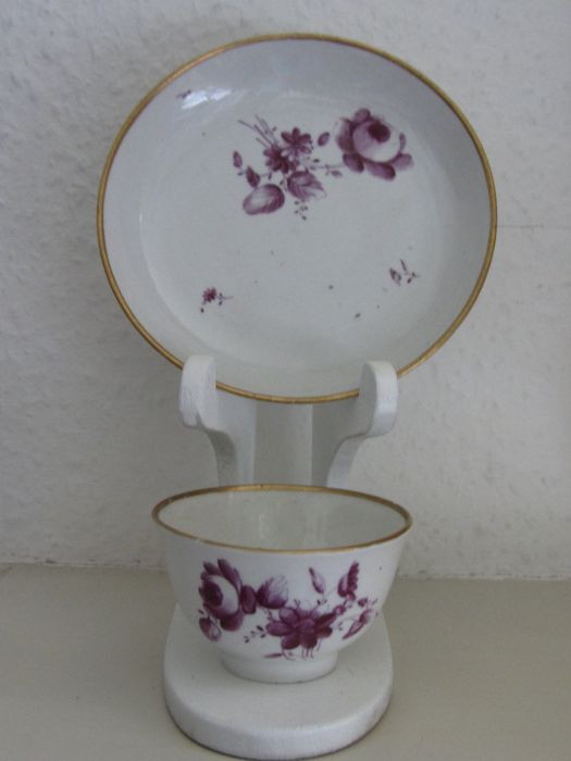 18th century cup and saucer with a beet red flower decoration and a golden stripe around the edge