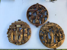 A series of three round Chinese carved and gold-plated wooden panels.