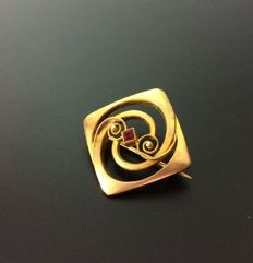Antique gold brooch with red stone