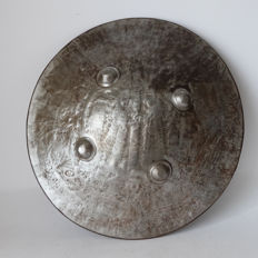 Metal shield, hammered decor of figures in architectural landscape