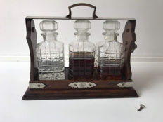An oak tantalus with three whisky decanters, England, 20th century