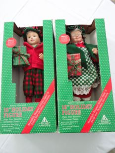 Two musical moving porcelain Christmas dolls in original packaging